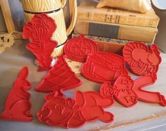 8 vintage Tupperware cookie cutters .... lil pig ... birthday cake ... jack o lantern ... bunny ... ginger man ... turkey ... Santa ... Tree