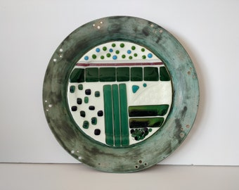 Vanilla and green fused glass sculpture within ceramic frame