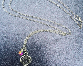 Silver key necklace with a red iridescent jewel accent.