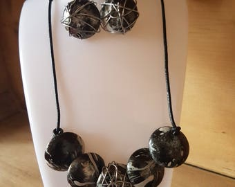 Contemporary black and white marble effect metal disc necklace on leather cord and matching drop earrings