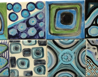 8 tiles handpainted with geometric motifs in blue tones