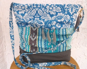 Boho tassel crossbody bag! Floral and Aztec prints mix it up on this ruched purse with tassel trim and purse charm. Blues and grays.