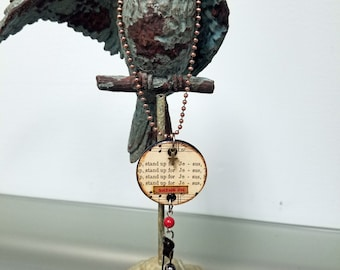 Heartsongs - Stand Up for Jesus is an altered wood poker chip with paper hymn snippets, metal findings and charms