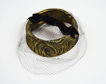 vintage fascinator hat: gold and black swirl with veil and velvet bow