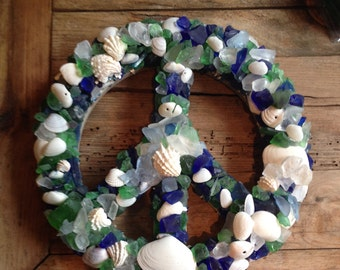 "This 12"" peace sign is adorned with sea shells along with sea glass. Shades of blues and greens give the image of the ocean and its purity!"
