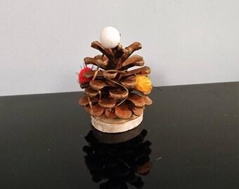 Pinecone Christmas ornament on birch slice