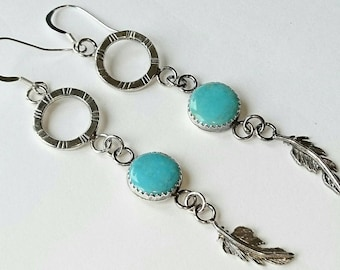 Sterling silver handmade dangle earrings with kingman turquoise cabochons and hand pierced feathers. Hallmarked in Edinburgh