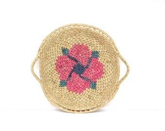 woven flat handle basket with pink pinwheel floral woven center and handles , grass coil tray style handle basket