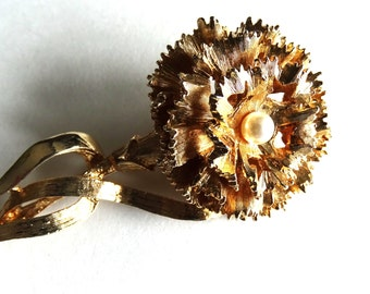 Gold tone carnation brooch. Pearl in center.Unsigned beauty but might be missing a part.