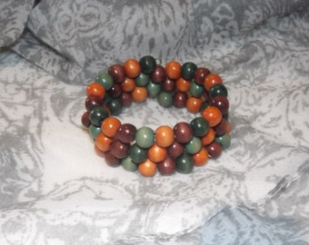 Bracelet of wood beads on memory wire, orange, brown, green