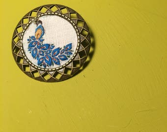 Peacock brooch, stamped and hand embroidered. 3 x 3 cm