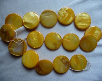 Mother of Pearl, 25mm Flat Round Coin, Shades of Yellow. Sold per 15 inch strand. There are 16 beads on the strand.