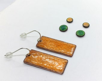 bright orange dangle earrings with green and yellow stud earrings
