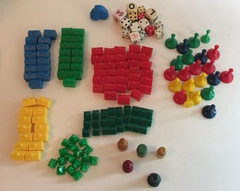 Vintage 70's lot of 143 game pieces. Monopoly houses, hotels, dice, plastic spacers, and wooden spacers.