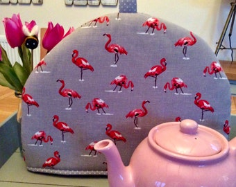 Tea cosy with fabulous pink flamingos on a grey cotton linen mix. Cheeky flamingos are a fun and quirky home accessory. Brightens up teatime