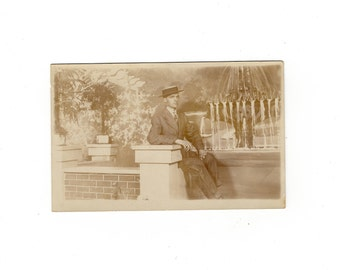 Man wearing hat with great backdrop, antique rppc photo