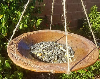 Hanging ceramic and hemp bird feeder.