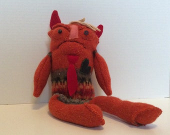 Handmade stuffed orange monster with devil horns and a black heart.