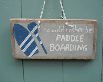 Paddle boarding sign hand painted on driftwood from a Solent beach.