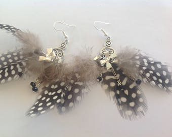 Earrings black speckled feathers with white connectors and bows and hooks in silver, silver chain, black beads.