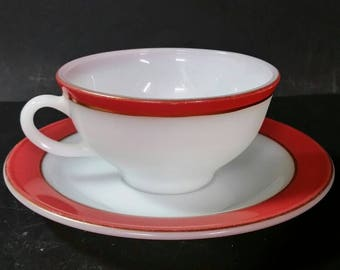 Vintage pyrex milk glass cup and saucer set.  White with red. Gold ring.
