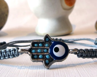 Handmade grey macrame bracelet with a hand shaped charm with blue stones and an evil eye