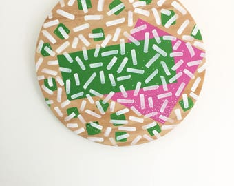 Abstract geometric confetti pattern painted on plywood circle