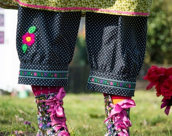 Black polka dot loose fit cuffed trousers with ribbon trim and crochet flower and leaves detail, elasticated waist