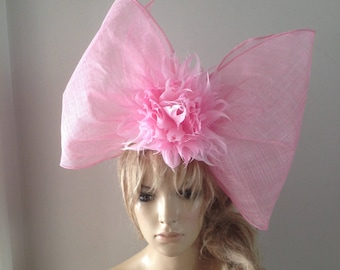 Large sculptured pink sinamay bow adorned with a brace of magnificent hand cut feather flowers.
