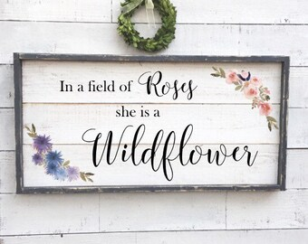 in a field of roses she is a wildflower, vintage wood sign