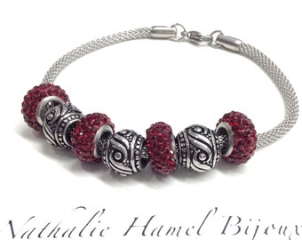 Pandora red swarovski beads and stainless steel beads mounted on a stainless steel cuff style bracelet.