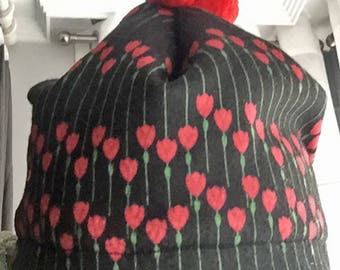Fleece hat for her, good gift. Black with red flowers. Red pom poms