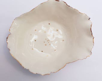 Delicate porcelain bowl with gold accents, organic shape