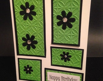 A handmade birthday card featuring green squares with black flowers