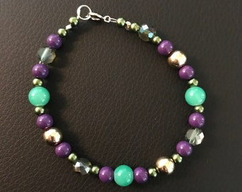 Beaded bracelet made with bright green beads, purple and gold