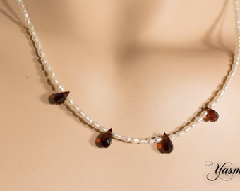 Freshwater cultured pearl with faceted Garnet