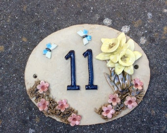 House numbers, address plaque, daffodil door number.