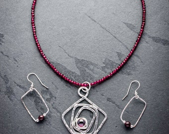Garnet and silver pendant on a necklace of garnet with matching garnet and silver earrings.