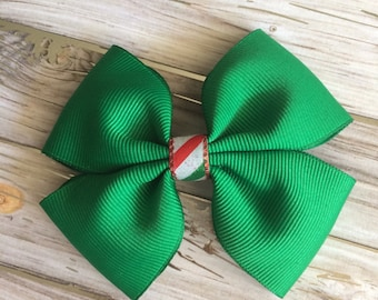 A handmade green holiday bow with a red, green and white center as an accent ribbon.