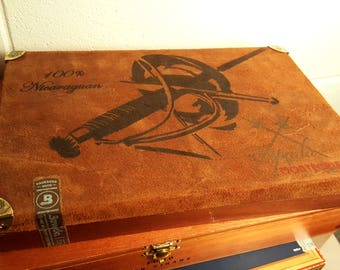 very fancy Montecristo empty cigar box in great condition swords on front no clasp, top feels leather-like