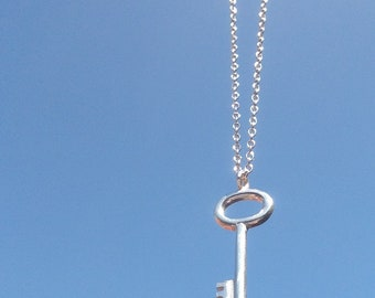 A completely handmade, small solid silver key pendant