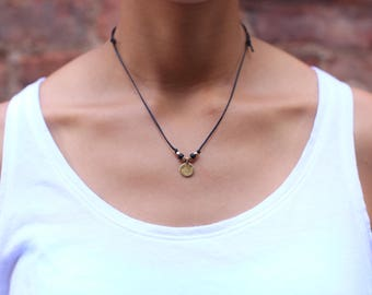 Solid brass Lotus symbol on a waxed cotton cord necklace. Wear 4 ways.