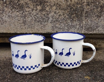 A pair of enamel vintage mugs in blue and white
