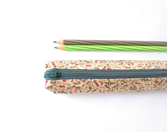 Small pencil case/zipper pouch  with small hearts, leaves and flowers on a light brown background, with a dark green zip