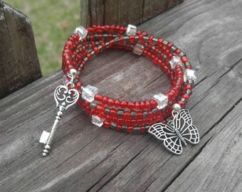 Red and black seed bead wrap bracelet. Butterfly charm and antique key. Memory wire.