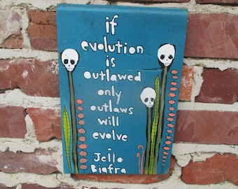 Jello Biafra quote art on salvaged wood, if evolution is outlawed only outlaws will evolve, skull flowers, evolution quote, Dead Kennedys