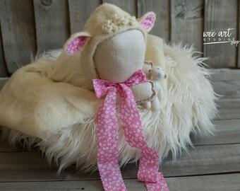 The White Lamb Bonnet with a pink ribbon