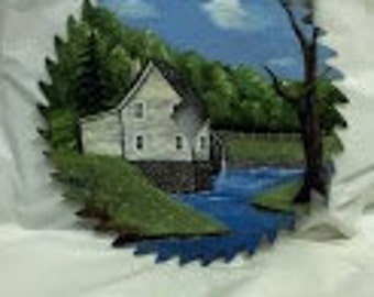"""8"""" Oil Painted Circular Saw Blade Depicting a Grey Bulding with a Water Wheel and a Stream in the Foreground"""