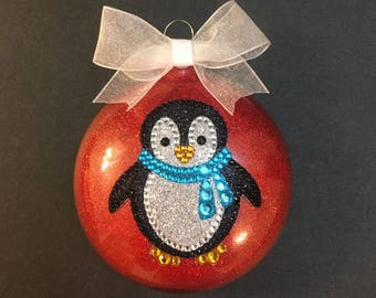 Sparkly red ornament with a glittery penguin and a little white bow
