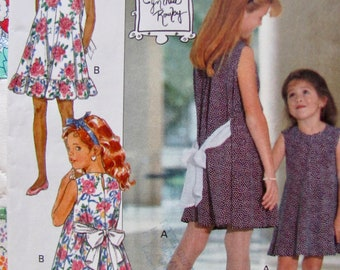 Butterick 6091, Girls Size 4,5 and 6, Loose Fitting, Slightly Flared Pullover Dress, Ruffled Hem, Back Ties Attached to Bow, Neck button
